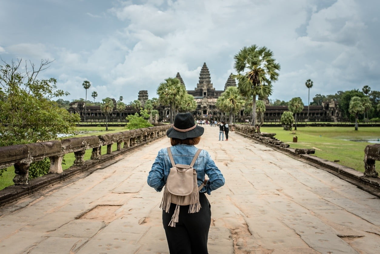 Women tourists wear jacket jeans walking into Angkor Wat landmark in Siem Reap, Cambodia. Angkor Wat inscribed on the UNESCO World Heritage List in 1992
